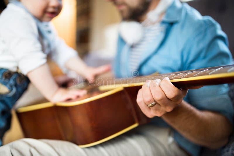 Niño pequeño en casa que toca la guitarra con su padre fotos de archivo
