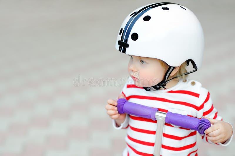 Niño pequeño en casco de seguridad con la vespa imagenes de archivo