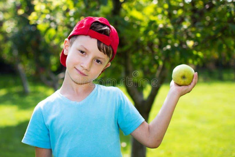 Niño pequeño en casquillo con la manzana fresca foto de archivo
