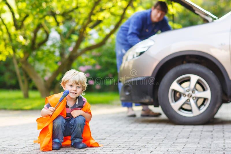 Niño pequeño en chaleco anaranjado de la seguridad durante su padre que repara el fam foto de archivo