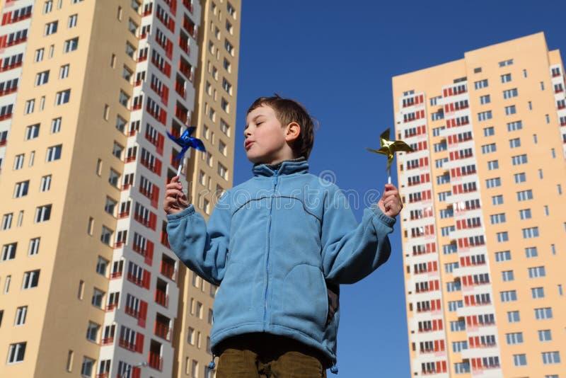 Niño pequeño en chaqueta con los pinwheels en sus manos foto de archivo