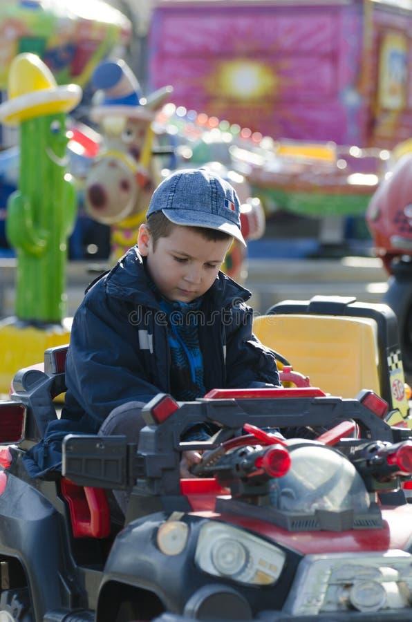 Niño pequeño en coche del carrusel foto de archivo