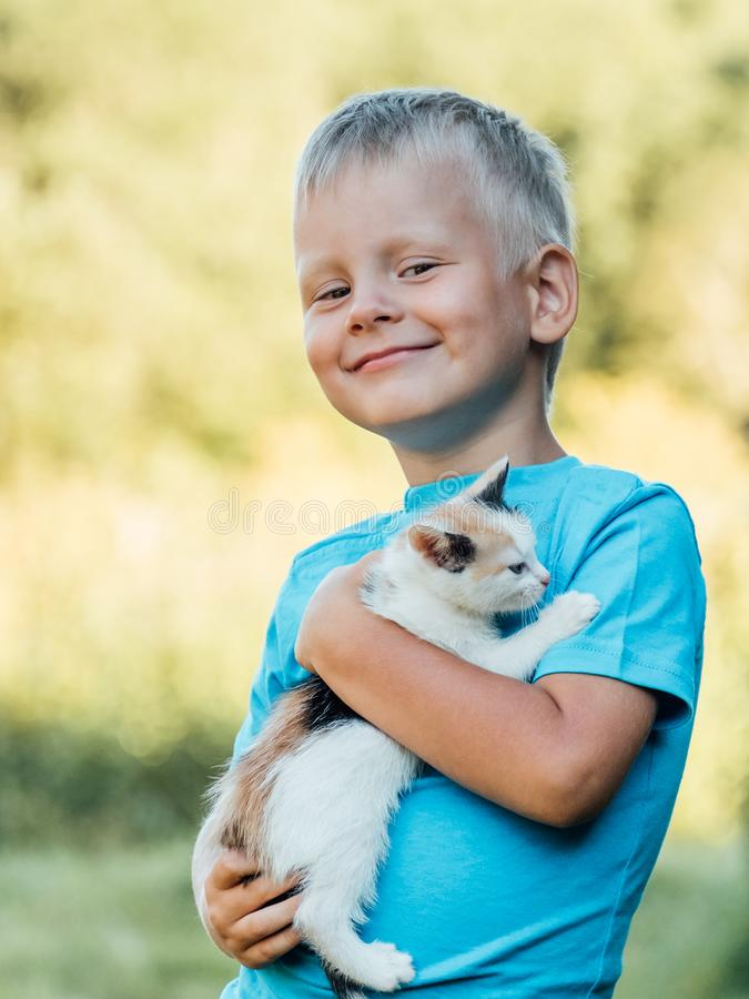 Niño pequeño en el campo que sostiene su gato mullido precioso del gatito foto de archivo libre de regalías