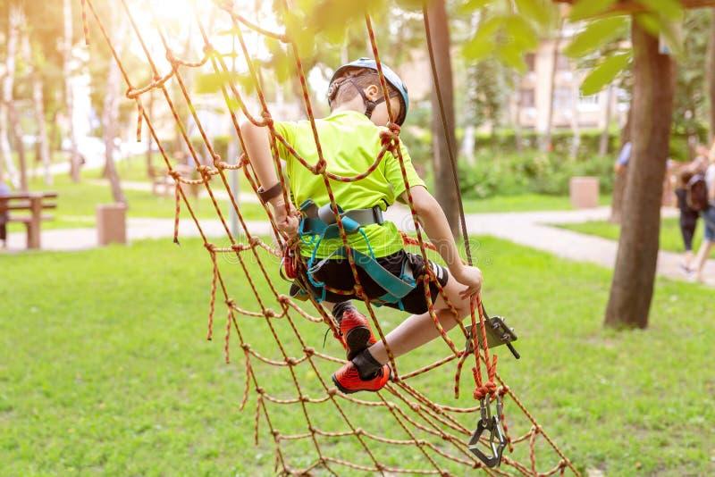 Niño pequeño en el equipo de seguridad que sube en la pared de la cuerda en el parque de la aventura Actividad al aire libre del  imagen de archivo libre de regalías