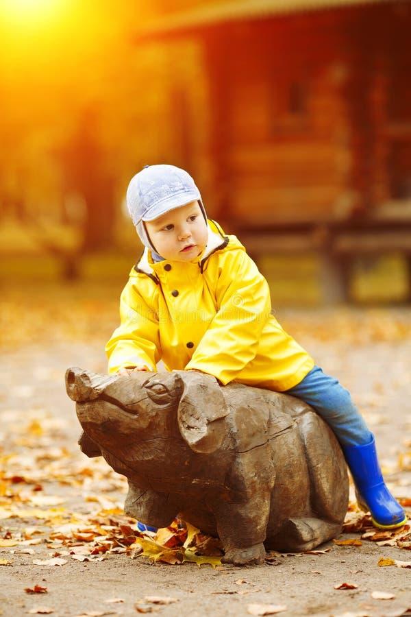 Niño pequeño en el fondo del parque del otoño Niño con una hoja de arce foto de archivo libre de regalías