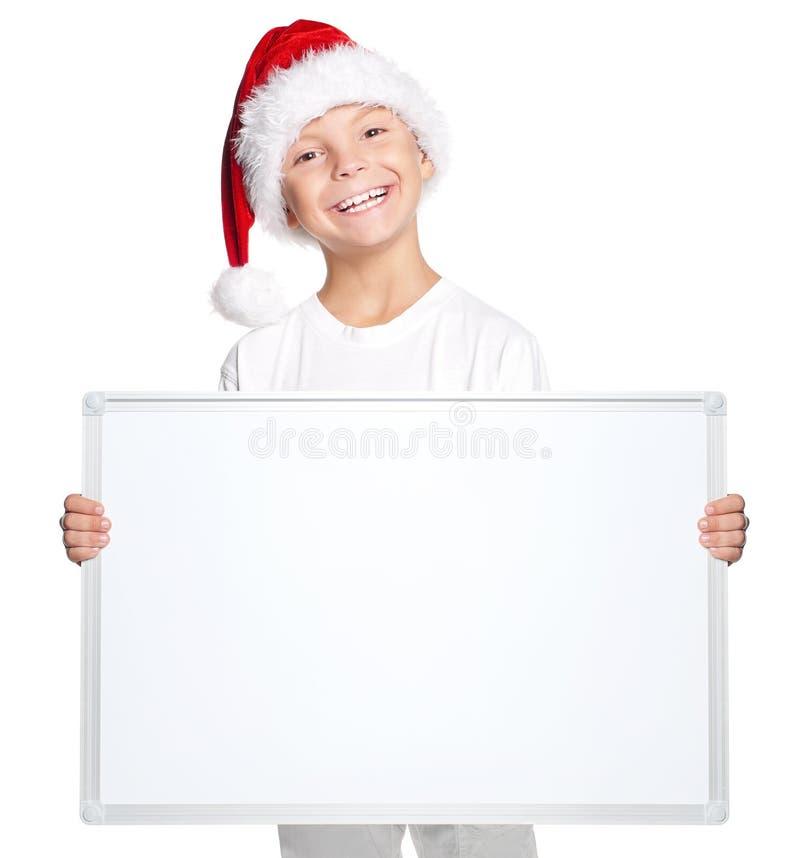 Niño pequeño en el sombrero de Papá Noel con el tablero en blanco fotos de archivo