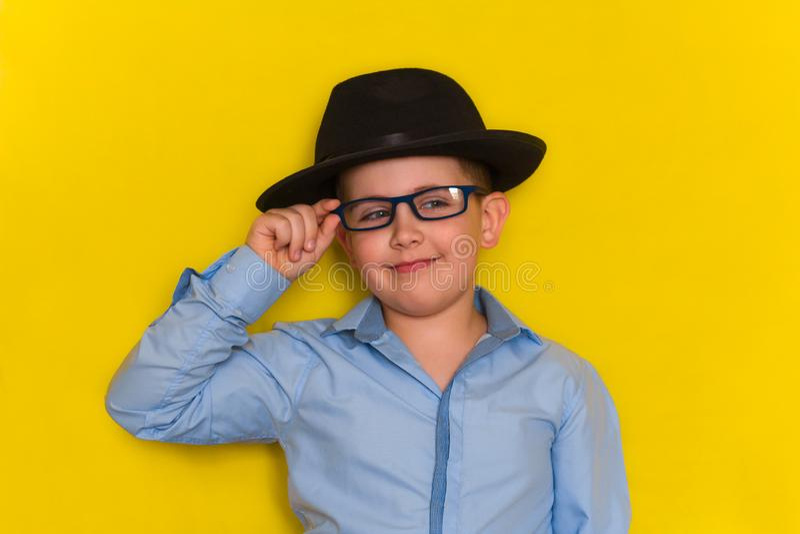 Niño pequeño en el sombrero negro y la mano púrpura sobre los vidrios, fondo amarillo de la tenencia de la camisa fotos de archivo libres de regalías