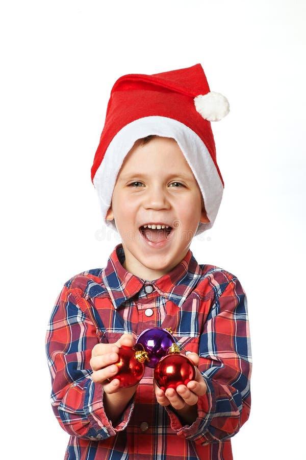 Niño pequeño en el sombrero rojo de Papá Noel con las bolas brillantes de la Navidad imágenes de archivo libres de regalías