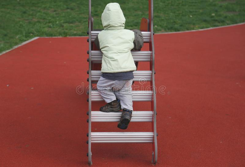 Niño pequeño en la chaqueta del otoño que sube en escalera imagenes de archivo