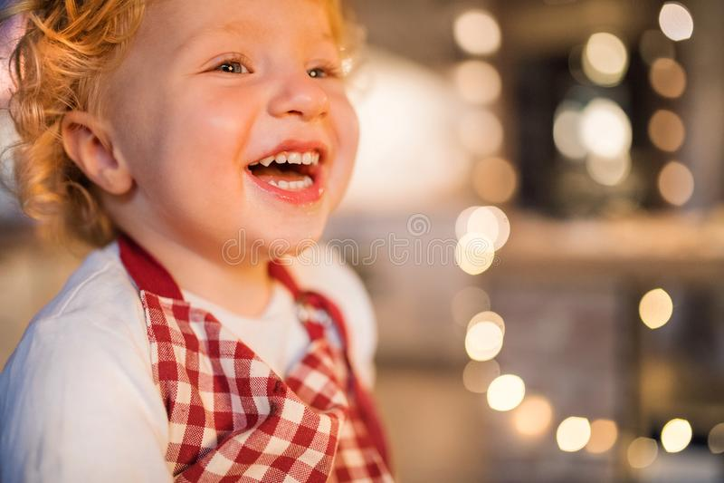 Niño pequeño en la cocina en el tiempo de la Navidad imagen de archivo