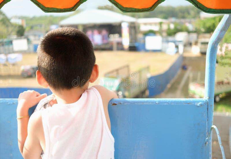 Niño pequeño en la noria que mira el fondo de la opinión de parque de atracciones de detrás escena imágenes de archivo libres de regalías