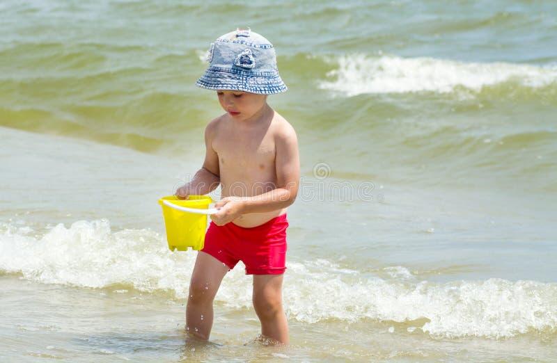 Niño pequeño en la playa que recoge el agua en un juguete del cubo, jugando con la arena foto de archivo libre de regalías