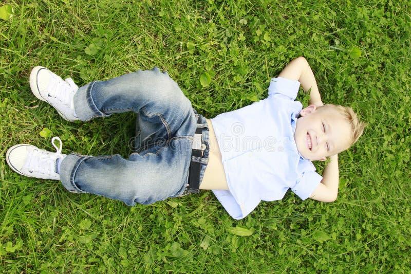 Niño pequeño en la sonrisa del prado imagenes de archivo