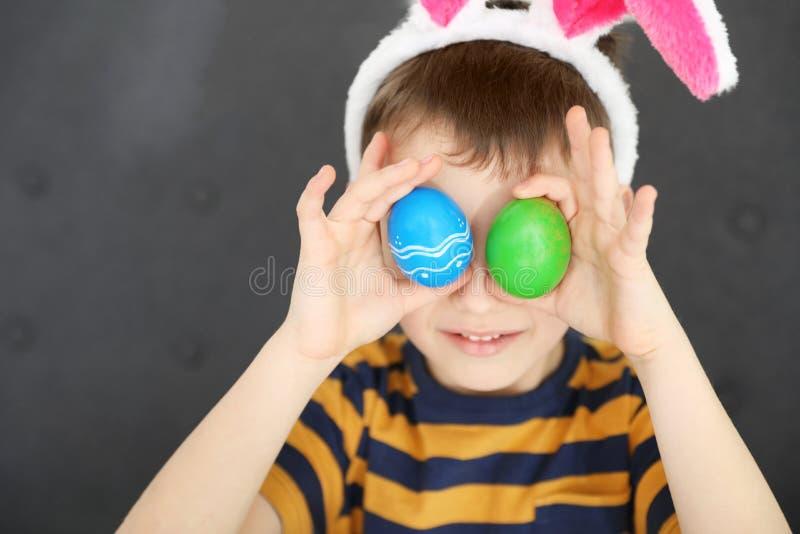Niño pequeño en la venda de los oídos del conejito que sostiene los huevos de Pascua cerca de ojos en casa fotografía de archivo