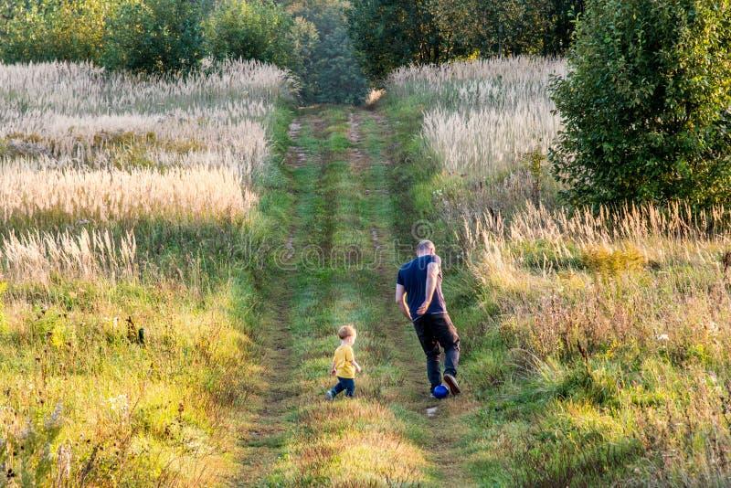 Niño pequeño en naturaleza con el padre, jugando tiempo fotos de archivo libres de regalías