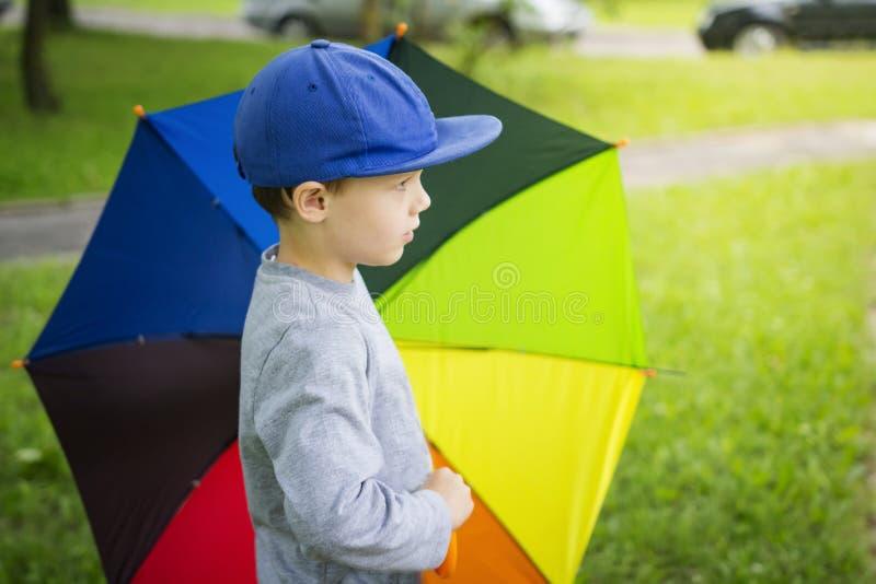 Niño pequeño en sombrero con el paraguas multicolor en parque después de la lluvia en día de verano soleado foto de archivo