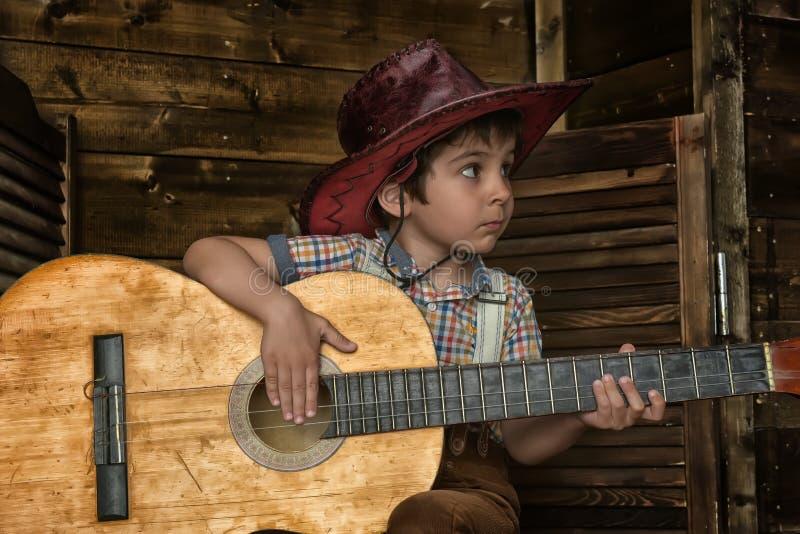 Niño pequeño en sombrero de vaquero con la guitarra fotos de archivo