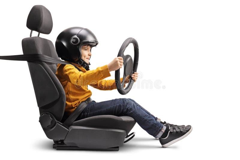 Niño pequeño en un asiento de carro con un casco que sostiene un volante imagenes de archivo