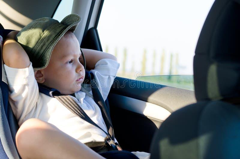 Niño pequeño en un asiento de la seguridad del niño foto de archivo