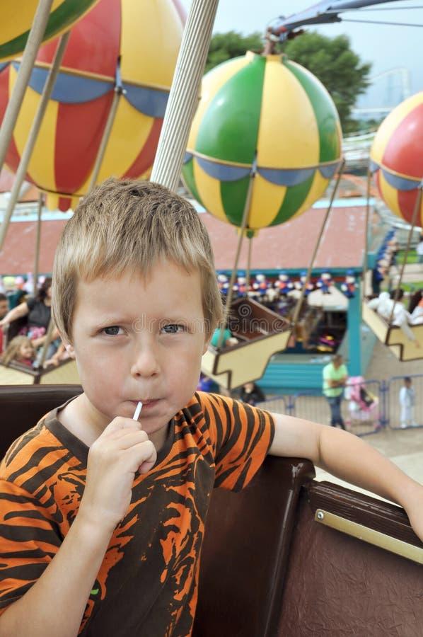 Niño pequeño en un carrusel en parque de atracciones foto de archivo libre de regalías
