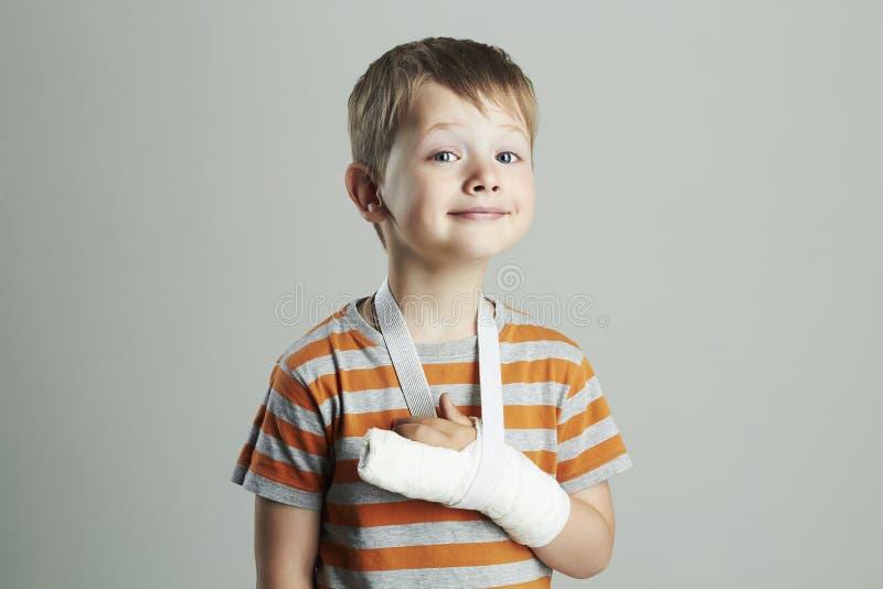 Niño pequeño en un castchild con un brazo quebrado niño divertido después del accidente fotografía de archivo