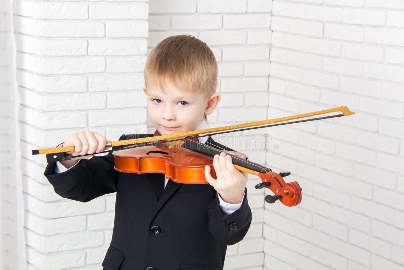 Niño pequeño en un traje que toca el violín fotografía de archivo
