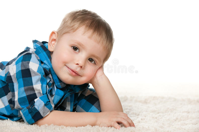 Niño pequeño en una camisa controlada en la alfombra imagen de archivo