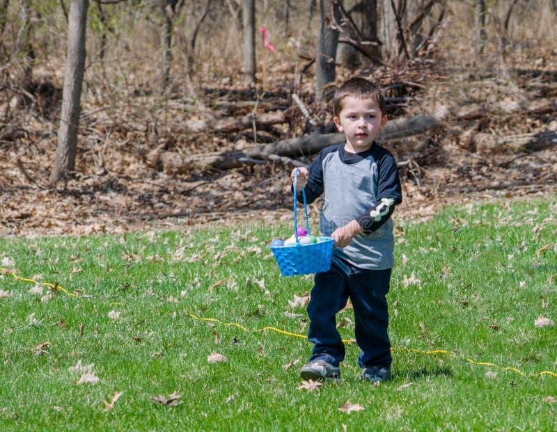 Niño pequeño en una caza del huevo de Pascua al aire libre foto de archivo