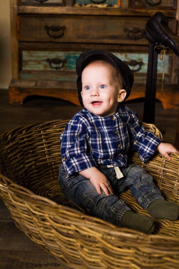 Niño pequeño en una cesta de Provence rural rústica hilarante, risa, sonrisa, alegría, ojos hermosos, azules fotografía de archivo libre de regalías