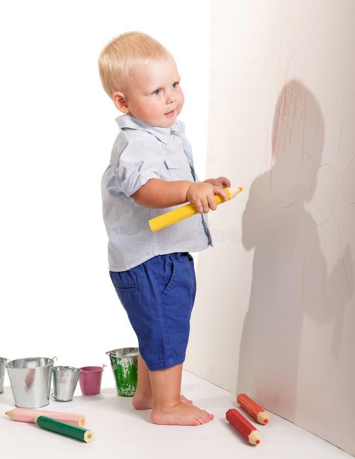 Niño pequeño encantador que se coloca que sostiene el lápiz amarillo para dibujar aislado fotos de archivo libres de regalías
