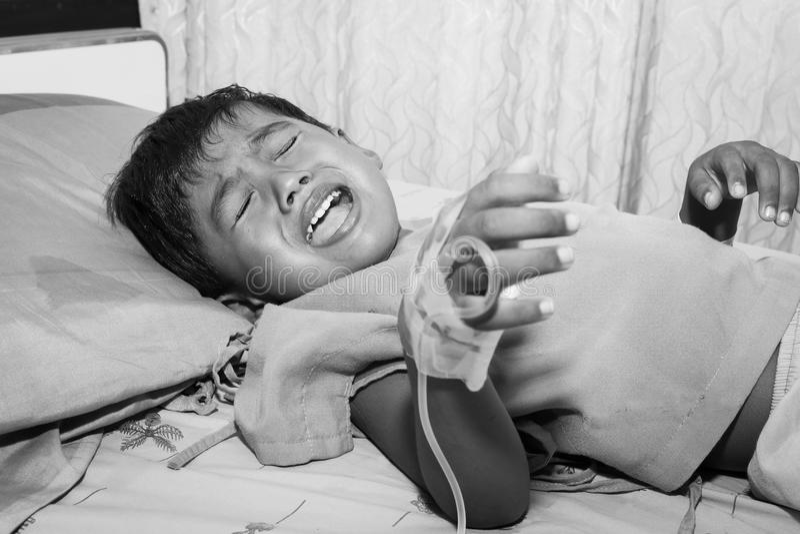 Niño pequeño enfermo y que llora en cama paciente imágenes de archivo libres de regalías