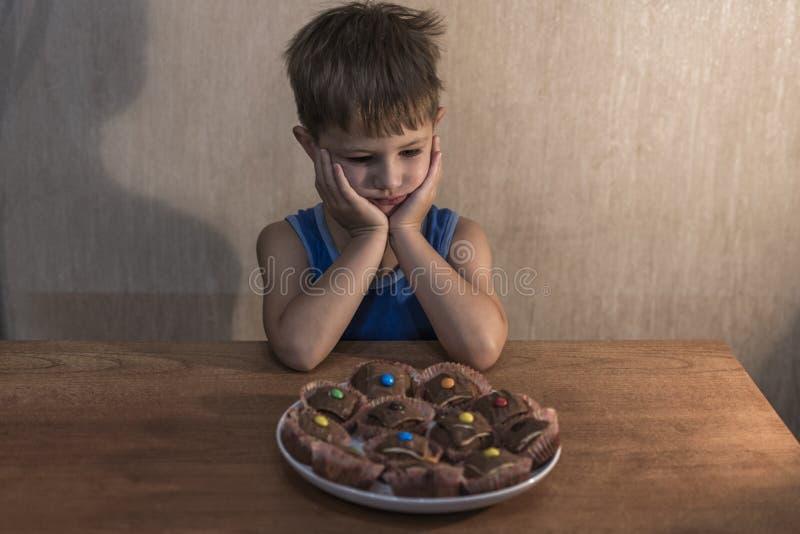 Niño pequeño enojado que se sienta en la tabla de cena imagen de archivo