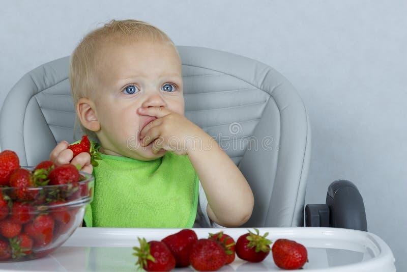 Niño pequeño feliz con las fresas en una silla del bebé, niño lindo que come las frutas maduras fotos de archivo