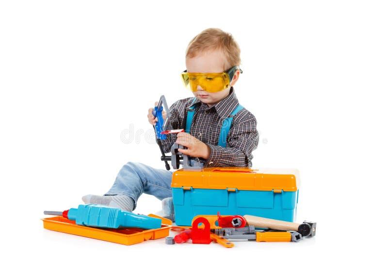 Niño pequeño feliz con las herramientas en el fondo blanco imágenes de archivo libres de regalías