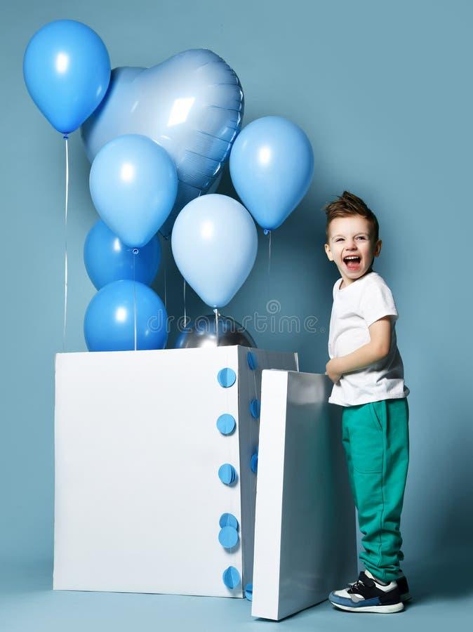 Niño pequeño feliz con los globos azules del color en colores pastel y la caja blanca vacía para la fiesta de cumpleaños imagen de archivo