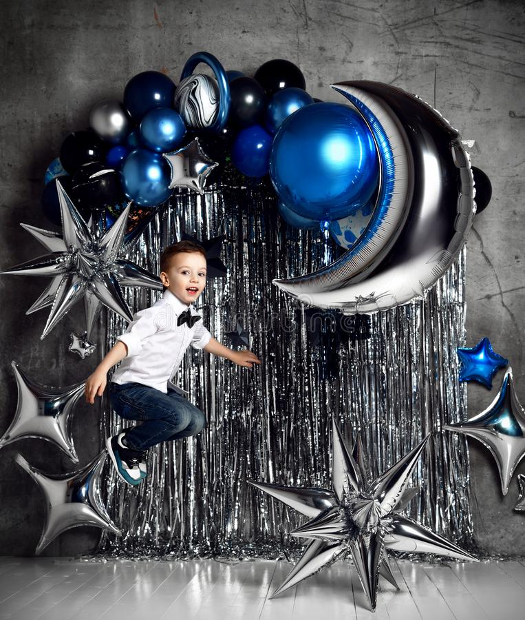 Niño pequeño feliz con los globos metálicos de plata y azules para la fiesta de cumpleaños con el texto libre fotos de archivo libres de regalías
