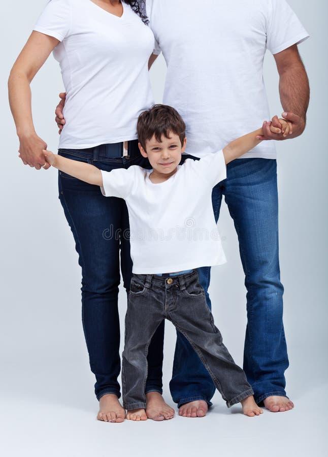 Niño pequeño feliz en la seguridad de su familia fotografía de archivo