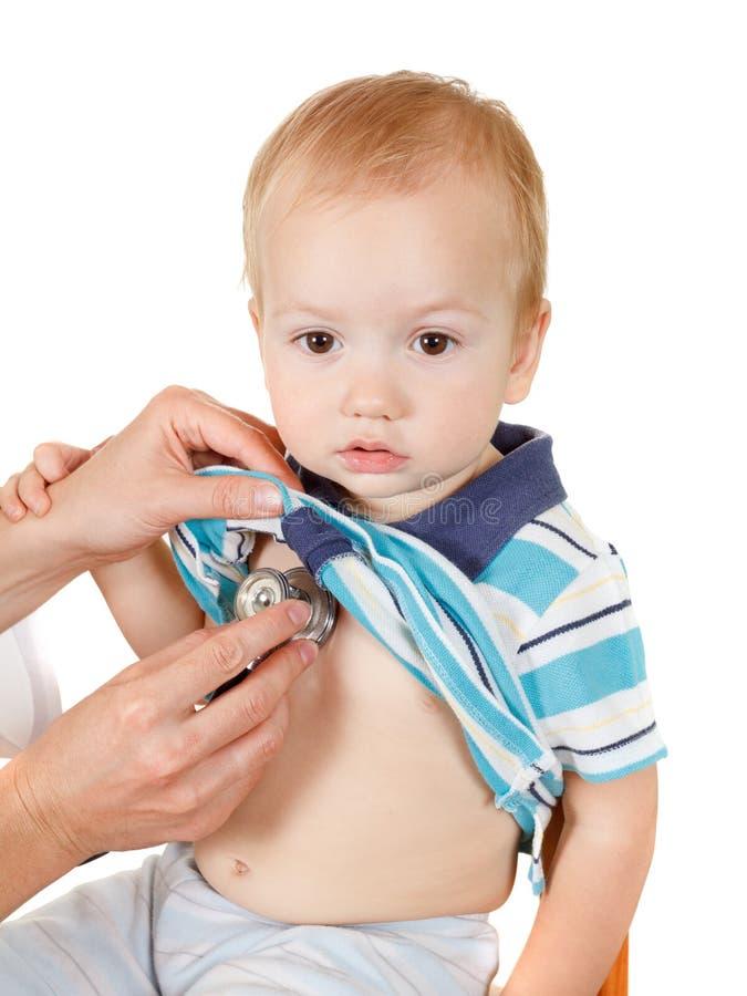 Niño pequeño feliz, examen de la salud en la oficina del doctor En el fondo blanco fotos de archivo