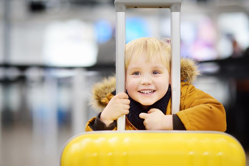 Niño pequeño feliz lindo con la maleta amarilla grande en el aeropuerto internacional antes del vuelo fotos de archivo libres de regalías