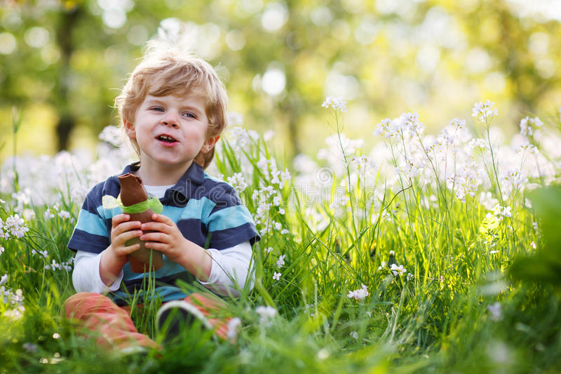 Niño pequeño feliz lindo que come el conejito del chocolate en el día de fiesta de Pascua fotos de archivo libres de regalías