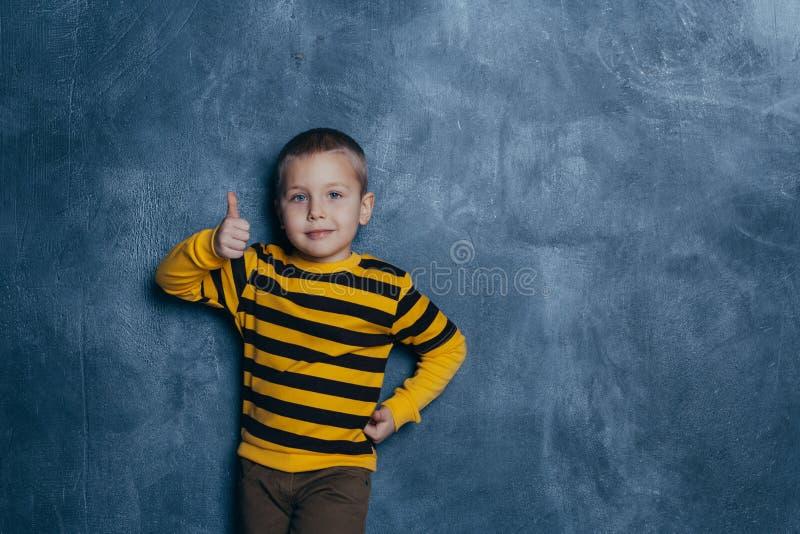 Niño pequeño feliz mismo que hace su risa de los fingeres fotografía de archivo libre de regalías