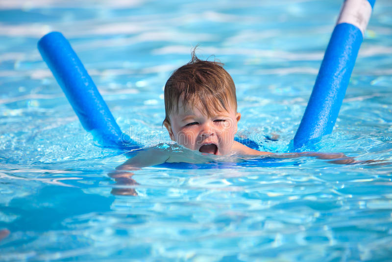Niño pequeño feliz que aprende nadar foto de archivo