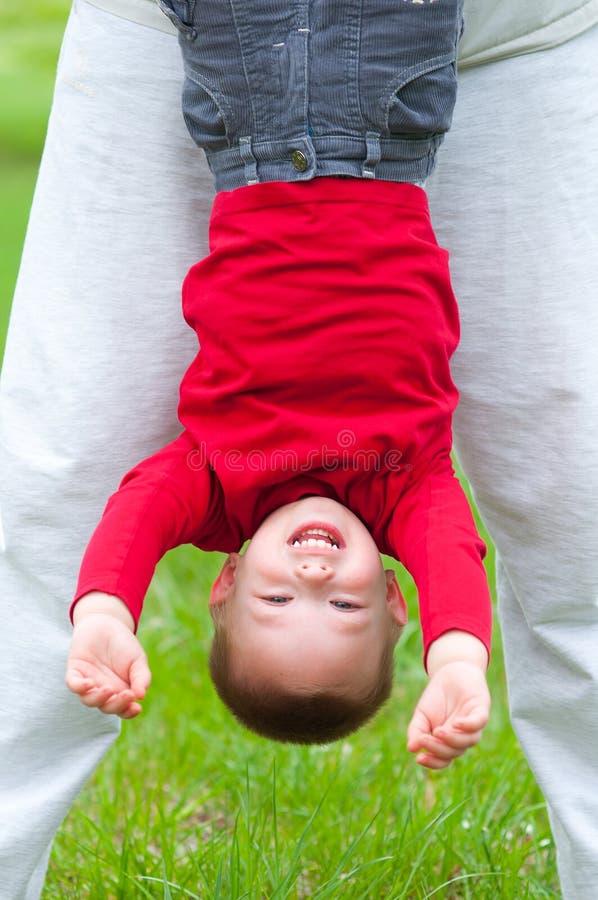Niño pequeño feliz que cuelga upside-down en prado fotos de archivo libres de regalías