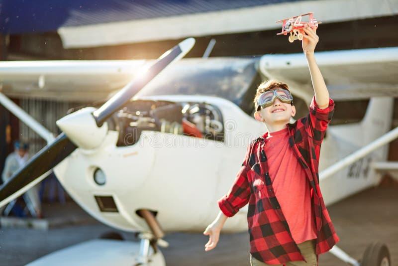 Niño pequeño feliz que juega con el pequeño aeroplano del juguete cerca de hangar imagen de archivo