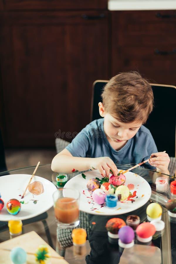 Niño pequeño feliz que pinta los huevos de Pascua, los niños y creatividad fotografía de archivo libre de regalías