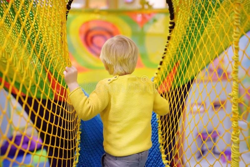 Niño pequeño feliz que se divierte en la diversión en centro del juego Niño que juega en patio interior fotografía de archivo libre de regalías