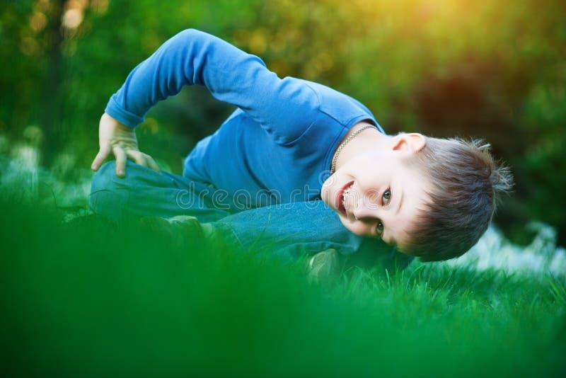 Niño pequeño feliz que se sienta en la hierba fotografía de archivo libre de regalías