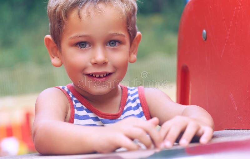 Niño pequeño feliz que sube en patio de los niños en día de verano hermoso imagenes de archivo