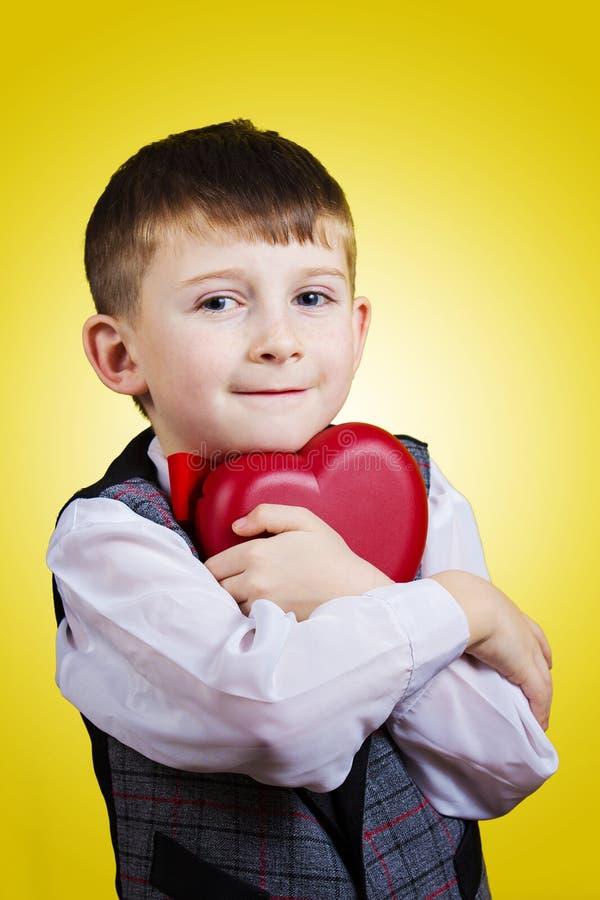 Niño pequeño feliz, sonriente que lleva a cabo el corazón rojo foto de archivo libre de regalías
