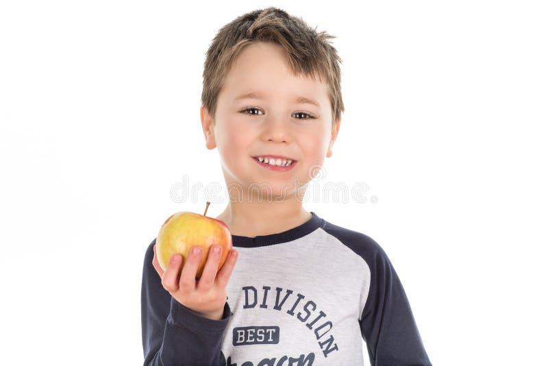 Niño pequeño feliz sonriente que sostiene una manzana foto de archivo